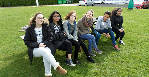 row of smiling young people sitting on a bench in a field