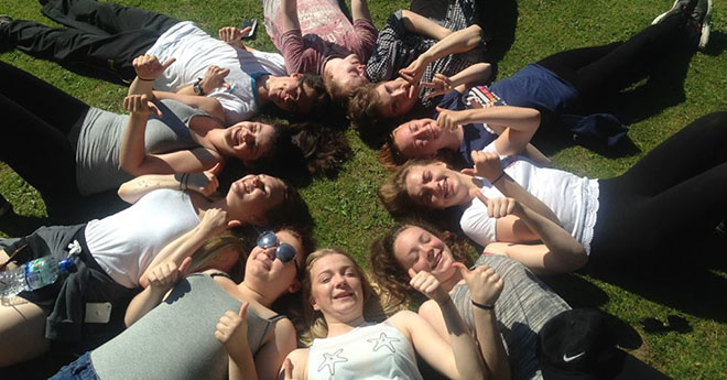 Young people lying in a circle in the grass looking up